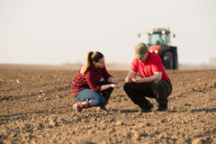 Young farmers examing planted wheat while tractor is plowing fi. Eld stock photos