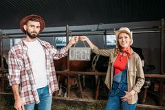 Farmers with open sign in cowshed Royalty Free Stock Image