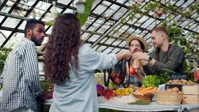 Young farmers selling organic vegetables to consumers in greenhouse market. Young farmers man and woman are selling organic vegetables to consumers in greenhouse stock footage