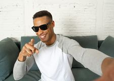 Young fashion african american blogger recording video blog or tutorial for his followers stock photo