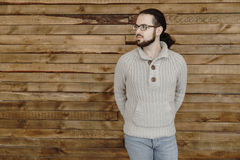 Young fashion beard man in eyeglasses, jeans and pullover on wood background. Fashion style beard man in eyeglasses, jeans and pullover on wood background Stock Photography