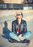 Young fashion beautiful girl in leather jacket, hat and sunglass Stock Image