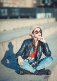 Young fashion beautiful girl in leather jacket with retro camera Stock Photos