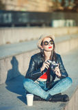 Young fashion beautiful girl in leather jacket with retro camera Stock Images