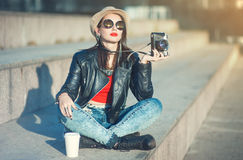 Young fashion beautiful girl in leather jacket with retro camera Royalty Free Stock Photography
