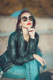 Young fashion beautiful girl in leather jacket and sunglasses Royalty Free Stock Photo