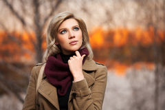 Young fashion blond woman in autumn forest. Young blond woman against an autumn nature background Stock Photo