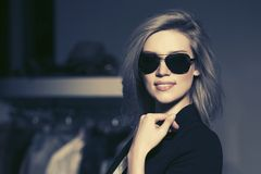 Young fashion blond woman in sunglasses in the mall interior. Young fashion blond woman in black blazer and sunglasses in the mall interior Stock Image