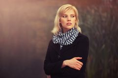 Young fashion blond woman in black coat walking in a fog outdoor Royalty Free Stock Photography