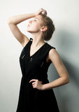 Young fashion blond woman in black dress Royalty Free Stock Photography