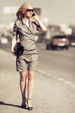 Young fashion blond woman calling on cell phone on city street Stock Images