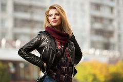 Young fashion blond woman in leather jacket on city street Royalty Free Stock Images