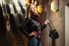 Young fashion blond woman in leather jacket with handbag Stock Photography
