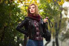 Young fashion blond woman in leather jacket in park Royalty Free Stock Photos