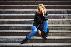 Young fashion blond woman in leather jacket sitting on the steps Royalty Free Stock Photography