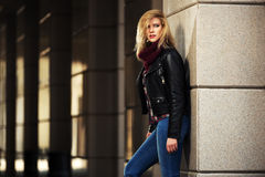 Young fashion blond woman in leather jacket at the wall royalty free stock photo