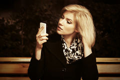 Young fashion blond woman looking at mobile phone Stock Photo