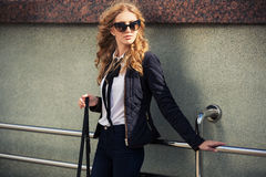 Young fashion blond woman in sunglasses. At the wall Stock Photos