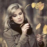 Young fashion woman in classic beige coat walking in autumn park royalty free stock photography
