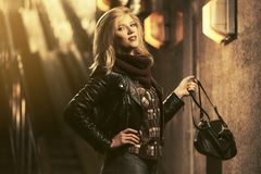 Young fashion blond woman wearing leather jacket in a subway stock images