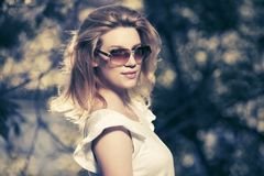 Young fashion blond woman wearing white top and sunglasses. In city park stock images