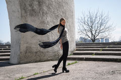 Young fashion blonde girl wearing long black scarf on the background of the futuristic building. Stock Photography