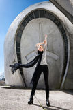 Young fashion blonde girl wearing long black scarf on the background of the futuristic building. Stock Image