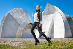 Young fashion blonde girl wearing long black scarf on the background of the futuristic building. Royalty Free Stock Photo