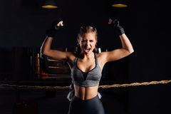 Young fashion boxer girl with boxing gloves screams emotionally rising arms. Young boxer girl with boxing gloves screams emotionally rising arms in victory sign royalty free stock photo