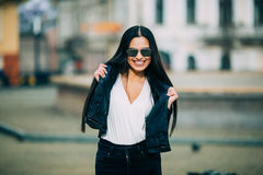 Young fashion brunette woman in sunglasses with jacket Royalty Free Stock Photos
