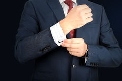 Young fashion  buisness man in  a blue/navy suit touching at his cufflinks. Business and office concept -  elegant young fashion  buisness man in  a blue/navy Stock Images