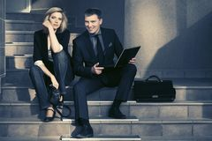 Young fashion business couple with laptop on the steps. At office building Royalty Free Stock Images