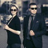 Young fashion business couple walking in city street Royalty Free Stock Images