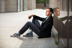 Young fashion business man with mobile phone sitting at the wall Royalty Free Stock Image