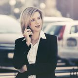 Young fashion business woman calling on cell phone on city street stock images