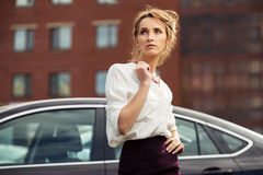 Young fashion business woman on city street next to her car Stock Photo