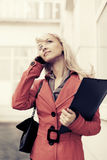 Young fashion business woman with a folder calling on cell phone Royalty Free Stock Photo