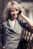 Young fashion business woman with a folder calling on cell phone. Outdoor Royalty Free Stock Photography