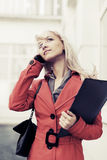 Young fashion business woman with a folder calling on cell phone Stock Photo