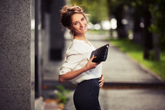 Young fashion business woman with handbag walking on city street Stock Images