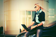 Young fashion business woman with laptop by car Royalty Free Stock Photos