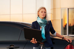 Young fashion business woman with laptop next to her car Stock Images