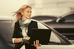 Young fashion business woman with laptop by her car Stock Photography