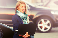 Young fashion business woman with laptop next to her car Royalty Free Stock Photography