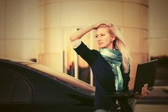 Young fashion business woman with laptop next to her car Royalty Free Stock Photos