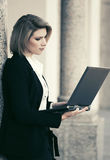 Young fashion business woman with laptop at office building Stock Photos