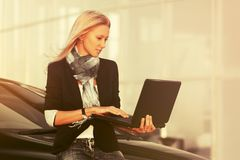 Young fashion business woman with laptop sitting on her car stock photo