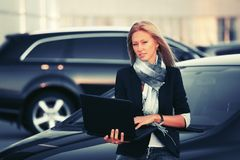 Young fashion business woman with laptop leaning on her car royalty free stock image