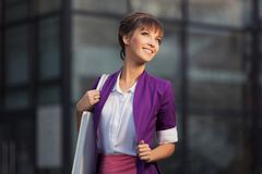 Young fashion business woman in purple blazer with handbag walking at the mall. Young fashion business woman with handbag walking at the mall  Stylish female Royalty Free Stock Photography