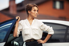 Young fashion business woman standing by her car Royalty Free Stock Image